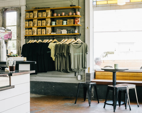 Interior photograph of Congregation Coffee Roastery and cafe. The interior shows one part of the cafe with a wall of merchandise that is 4 shelves tall stocked with multiple 12oz bags of coffee, coffee mugs, local guide books, hand printed tea towels, jars of local jam, and a row of hanging tshirts at the bottom. The tshirts are a variety of branded Congregation Coffee Roasters with the Trio of Alligators for their namesake - A congregation of Alligators is the collective noun.