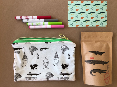 "Image of a 6""x 10"" zipper pouch with an allover print. The print is alligators and pelicans dressed with bow ties and bowler hats. There are also ice cream cones and fern fronds and the Sundae Best logo."