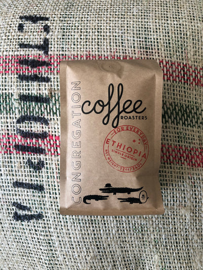 A 12oz bag of coffee is photographed on top of a burlap coffee sack. The coffee bag is brown kraft with a black hot stamp leaving a shiny black print of the company name and branded logo of 3 alligators. The Print says Congregation Coffee Roasters. There is also a round red stamp in the middle with the specific coffee inside the bag - the Ethiopia Single Origin - it says.