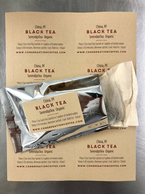 Photograph of one Big 1.5 ounce tea bag half in and half out of a silver freshness package. The bag and the tea are photographed on top of a sheet of Tea labels with brew instructions.