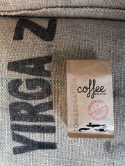 "Photograph of a 12oz bag of whole bean coffee. The bag is brown kraft paper with Congregation Coffee's classic 3 alligator logo and a red circular Ethiopia single origin stamp on the front. The bag is on a burlap coffee sack with the print ""Yirga Z"" on it."