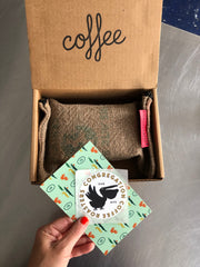 Brown cardboard coffee gift box with an upcycled coffee burlap zipper pouch with a 12oz bag of coffee inside. A hand in the image hold a Congregation Coffee Alligator patterned postcard and a pelican sticker  that is included in the box.