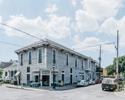 Landscape photograph of a big New Orleans style building with a corner store  that is the location of Congregation Coffee's Roastery. The sky is blue with big puffy white clouds. The photograph includes the intersection of the street, a streetlamp, 3 outside sidewalk tables, and cars parked. The building is in the residential area of Algier's Point on the West Bank of New Orleans.