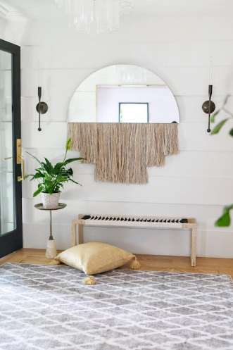 Grey trellis rug in the entryway with wooden bench and hanging wall decor