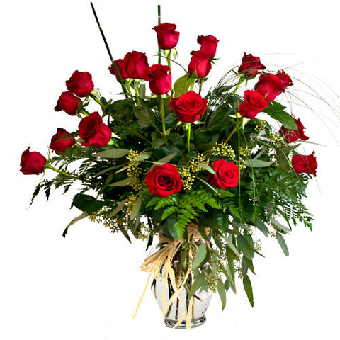 24 long stem red roses surrounded by greens in a designer vase wrappped with raffia