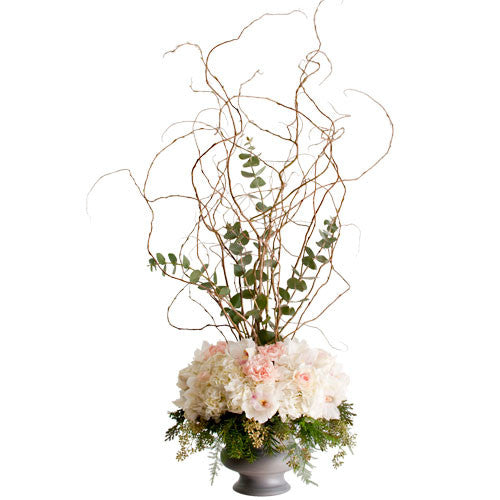 flower arrangement in urn with flowers around opening and curly willow branches coming up from the center