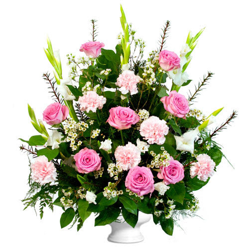 Triangle shaped arrangement in a white urn with white glads and pink carnations and roses