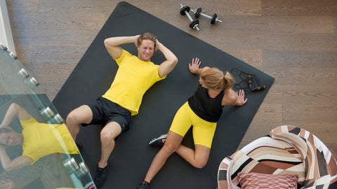 man and woman working out on exercise mat