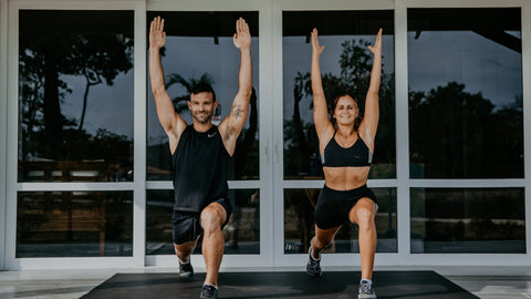 man and woman raising hands while exercising on large exercise mat