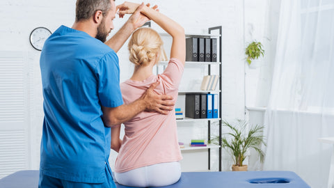 chiropractor helping a woman bad posture with waist trimmer