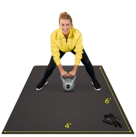 woman using Active Gear's best workout mat in black using home workout essentials kettle bell and skipping rope