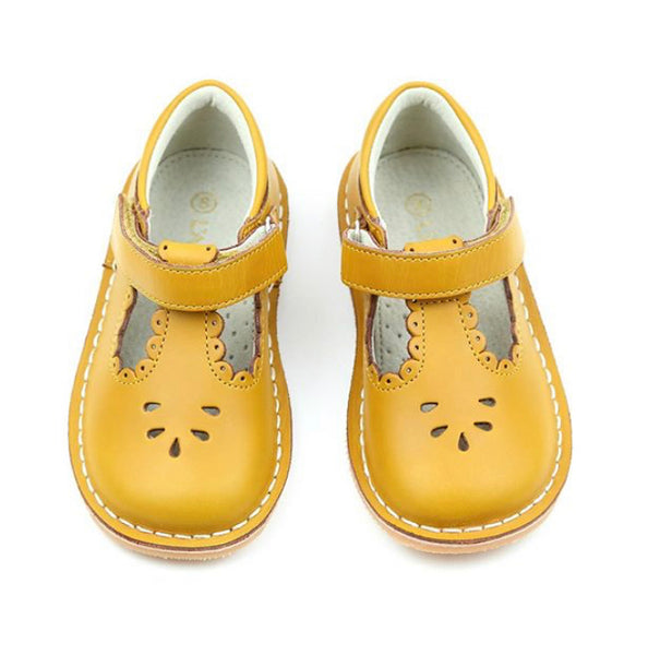 Angie is a vintage inspired shoe in the loveliest golden hue. The scalloped detail just sweetens up every outfit.  For those of you whose little one is outgrowing the Dottie,  fret not because Angie is an extension of the darling style!   This mustard leather offers a unique patina and a sturdiness that can withstand the greatest adventures.  Note: for an added touch, pair with our socks.