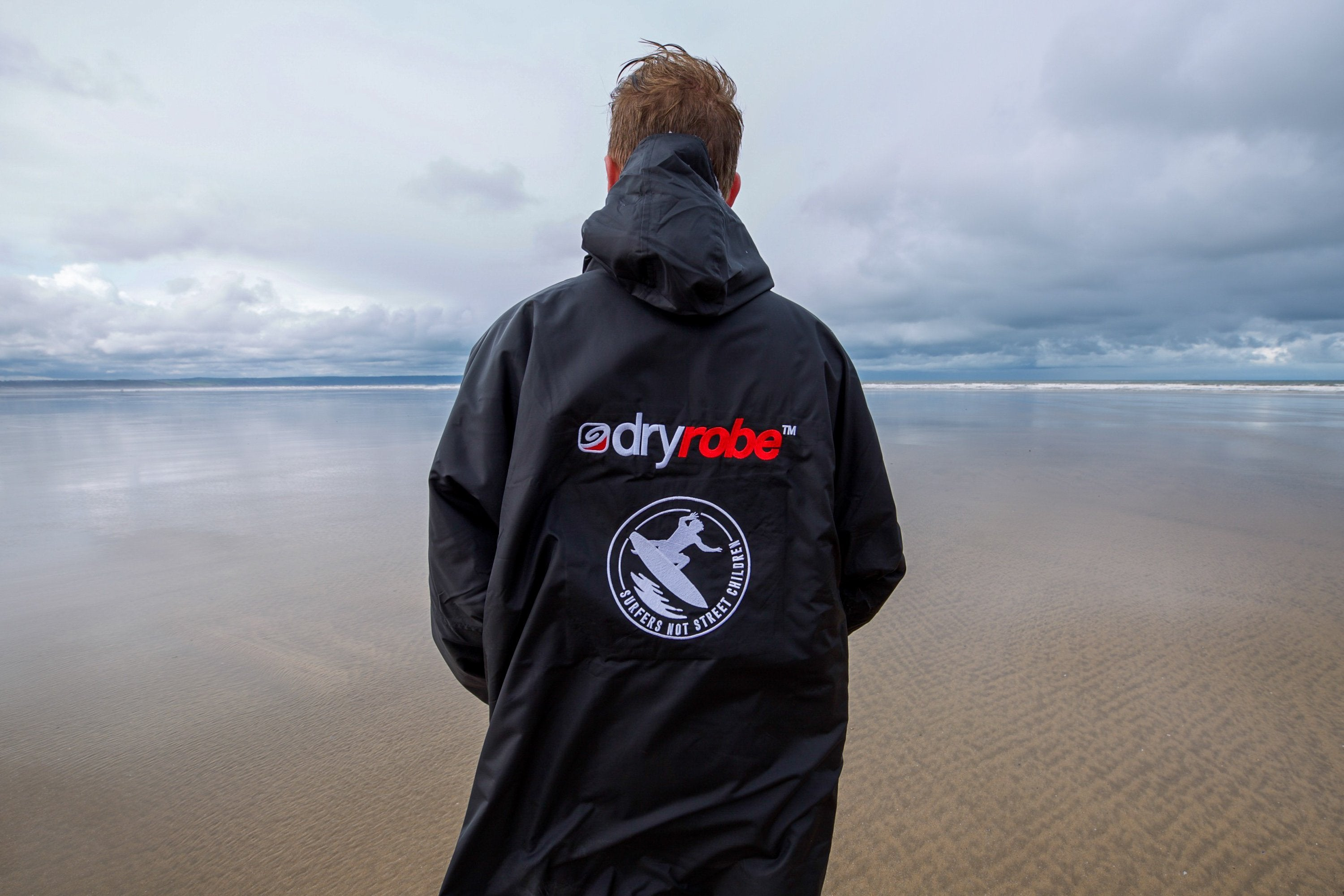 Big wave surfer Andrew Cotton modelling the official Surfers Not Street Children dryrobe