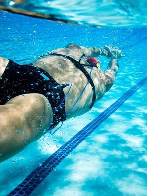 A female swimmer is streamlined underwater while listening to music from a waterproof phone case and headphones made by H2O Audio.