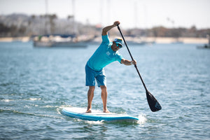 An athletic man wearing blue shorts stand-up paddleboards in a harbor while listening to music and using waterproof headphones from H2O Audio.