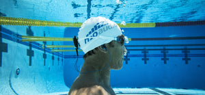 A man in a swim cap is submerged in a swimming pool while listening to music from the Stream waterproof MP3 player made by H2O Audio.