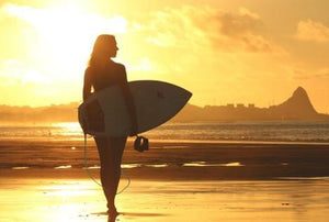 An attractive, athletic woman walks toward the setting sun while holding a surfboard.