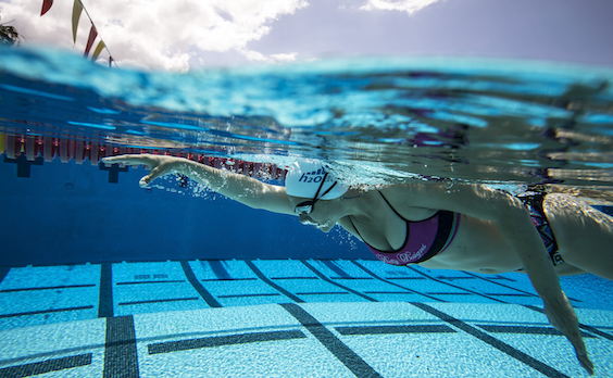 A female swimmer reaches forward during the pull phase of freestyle stroke. She's wearing a two-piece swimsuit and listening to music as she swims.