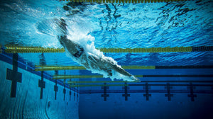 A male swimmer dives under the water while wearing custom waterproof headphones made by H2O Audio. Listening to music helps many swimmers to stay motivated during work outs weight-loss and relaxation.