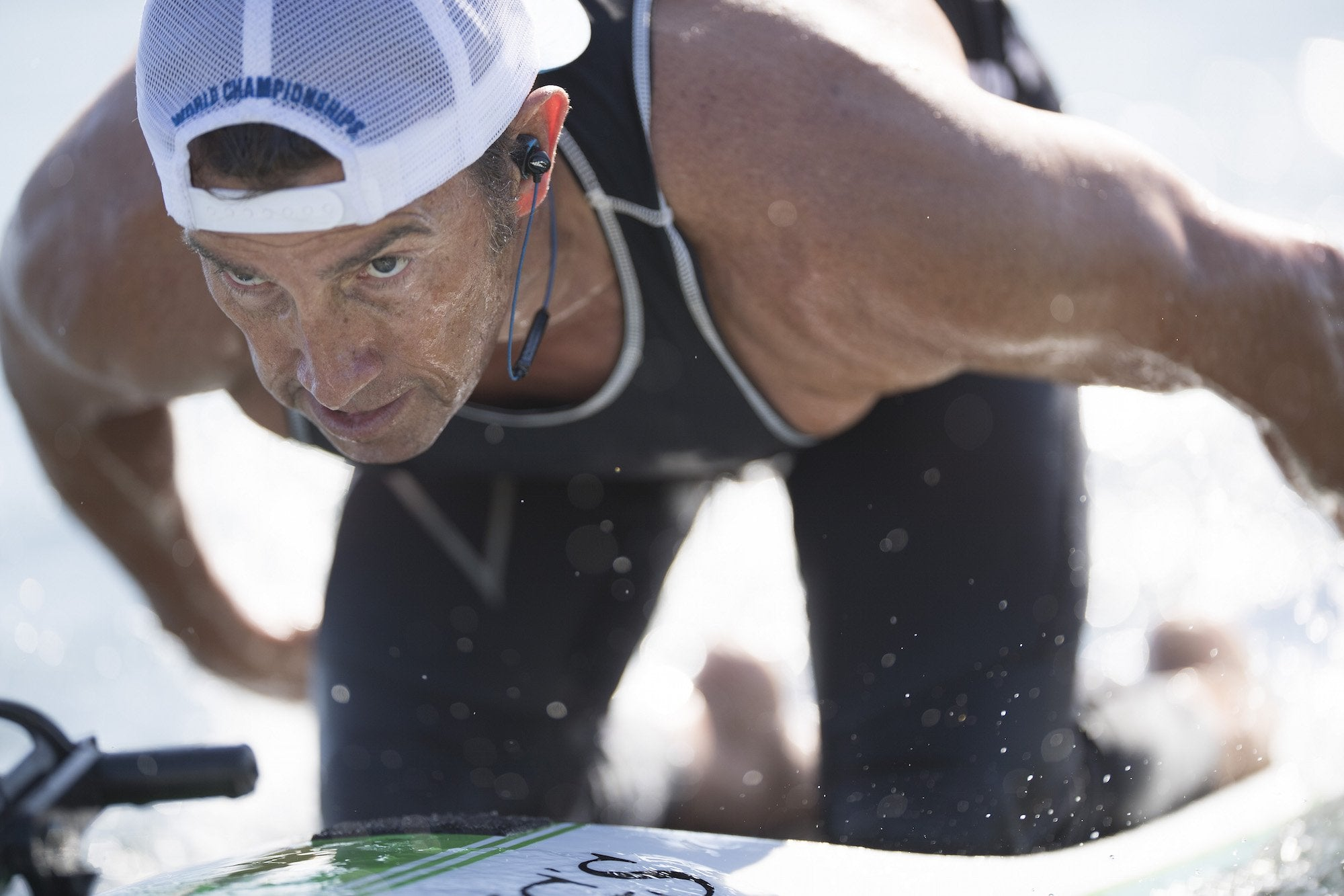 A male focuses ahead while paddleboarding on his knees. Waterproof headphones and music players (or waterproof phone cases) make it possible for ocean athletes to listen to music while working out, without the risk of damaging their devices.