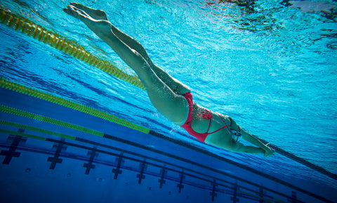 A female swimmer glides underwater in a swimming pool.