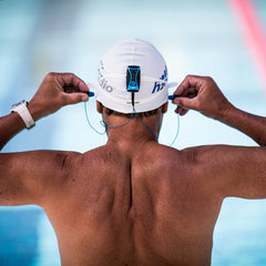 There are many ways to swim while using Bluetooth, however it takes some understanding of the technology and your devices. This image shows a man preparing to swim with a waterproof music player and headphones from H2O Audio.