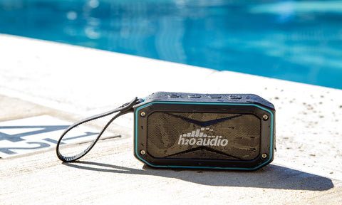 The Float is a small waterproof Bluetooth speaker. It's shown here on the deck of a swimming pool. It's also perfect for other environments that could expose technology to water, like lakes, rivers and the beach. It's made by H2O Audio, a company based in Southern California.