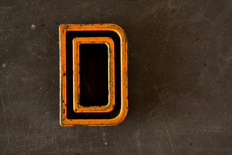 "Vintage Industrial Letter ""D"" Black with Light Orange and Blue Paint, 2"" tall (c.1940s) - ThirdShiftVintage.com"
