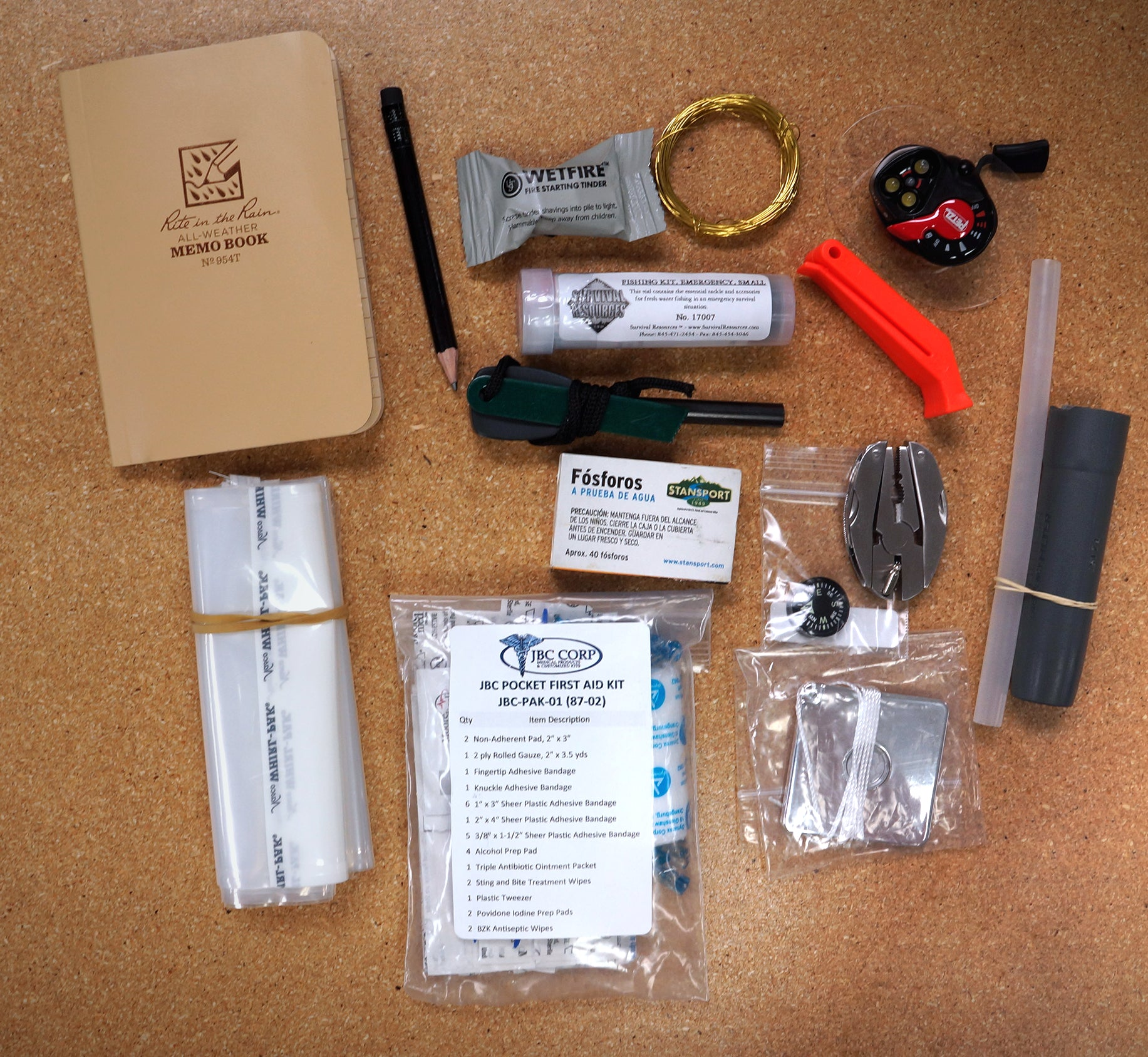 The contents of the JBC Survival Tin displayed on a table.