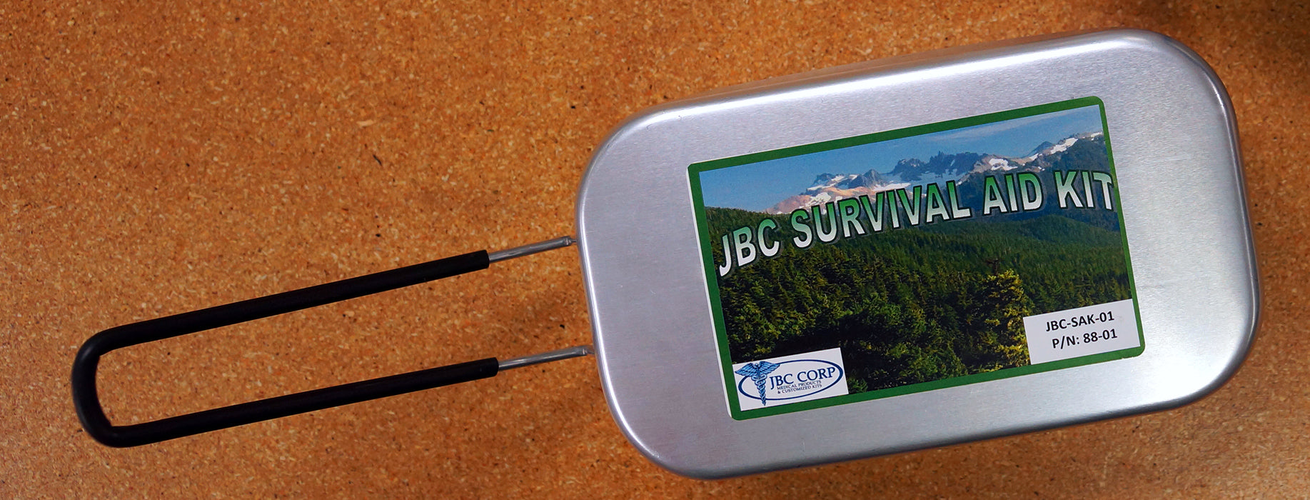 The JBC Survival Aid Tin with the handle extended.
