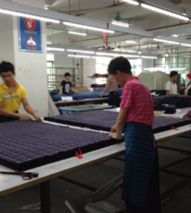 Tani employees cutting fabric for production
