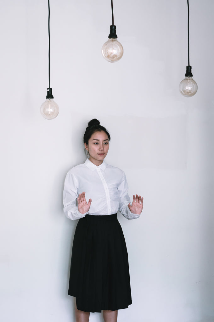 Nora shirt worn with pleated skirt