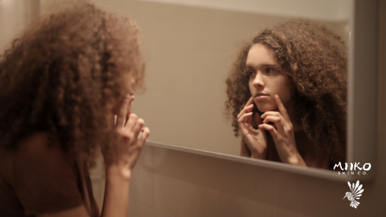 girl with big curly hair looking into mirror