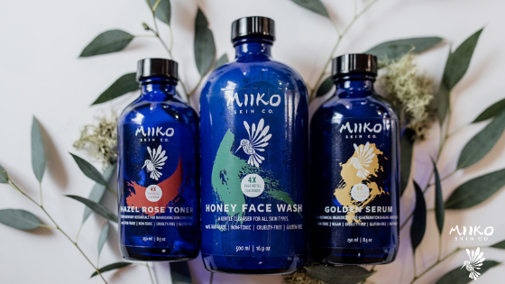 Three bulk blue glass Miiko bottles over top of some green leaves, shot against a white background