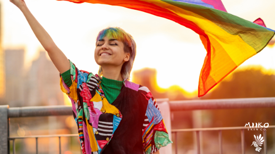 Person with rainbow dyed hair is smiling with their eyes closed and holding a Pride flag above their head. The sun is setting in the background behind them.