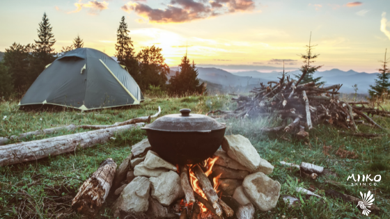image of a campsite up on a mountain. There is a pot cooking over a fire in the foreground, and a tent set up in the background. The whole campsite is overlooking a beautiful mountain valley and the sun is setting in the background