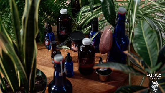 Miiko Skin Co's skincare products sitting on a wooden tabletop with tropical plants surrounding.
