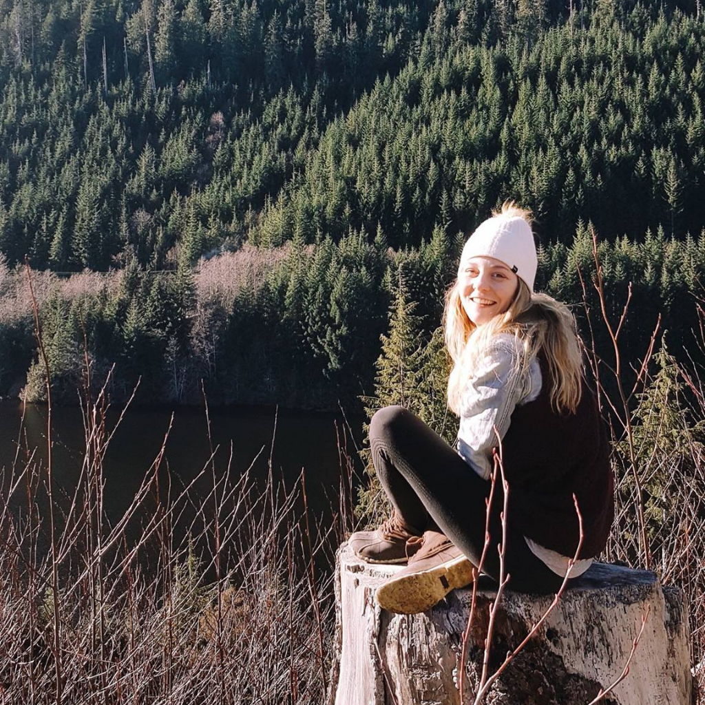 woman sitting on tree stump in front of forest & hills