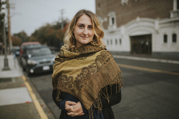 Girl with gold scarf standing on street
