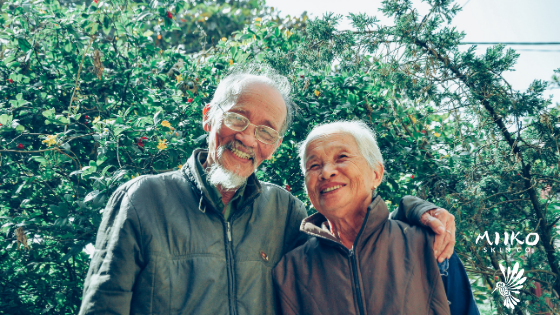 elderly couple with their arms wrapped around each other smiling in front of a tree