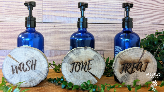 three large bulk blue bottle with pumps. Each bottle has a wooden coaster in front of it, and there is greenery in the background