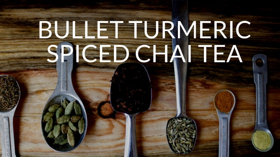 wood platter with metal tablespoons holding various eastern spices - text bullet turmeric spiced chai tea