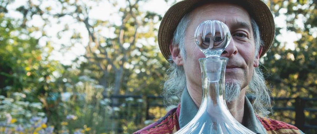 Mystic man in nature looking through glass bottle