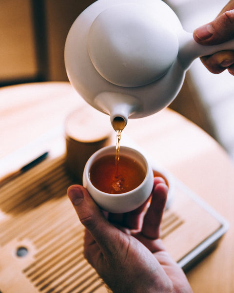 Close up image of herbal tea being poured into a small tea cup.