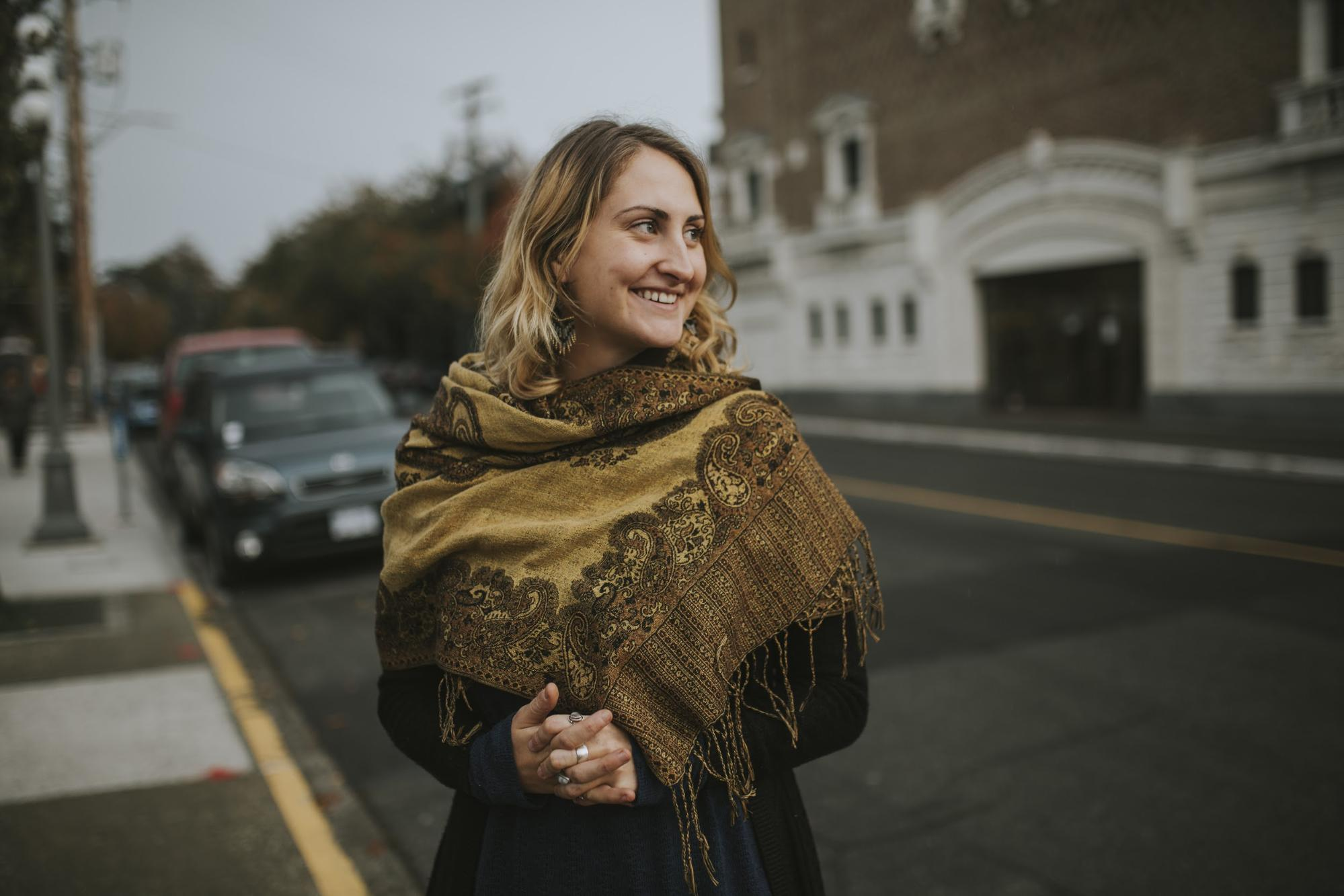 woman with scarf smiling away from camera on street
