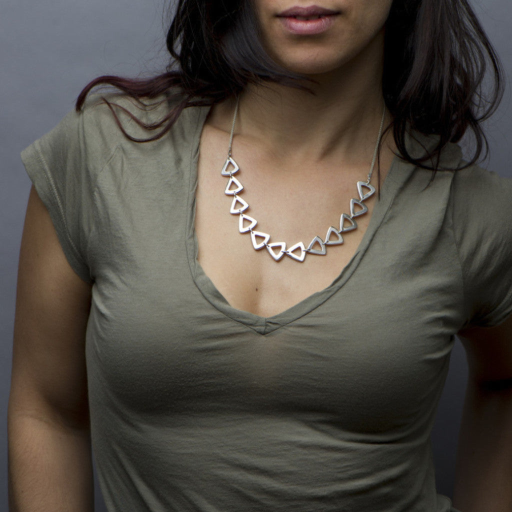 Beveled broadly curved triangles drape across the chest in this demi sterling silver necklace. Handmade by Sky Phaebl.