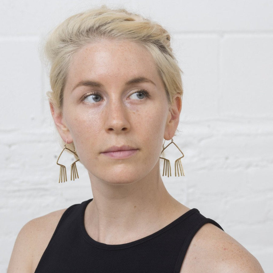 Model wears Sky Phaebl bronze and gold open, obtuse triangular earrings with hammer textured fixed fringe.