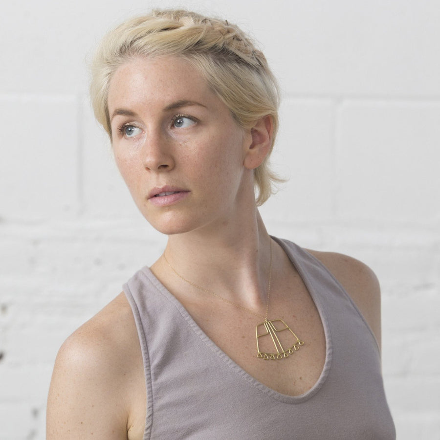 Model wears bronze Sky Phaebl curved trapezoid pendant lined with triangular fixed fringe and featuring linear filigree detail, on a fine gold-filled chain. Lays just below the clavicle.