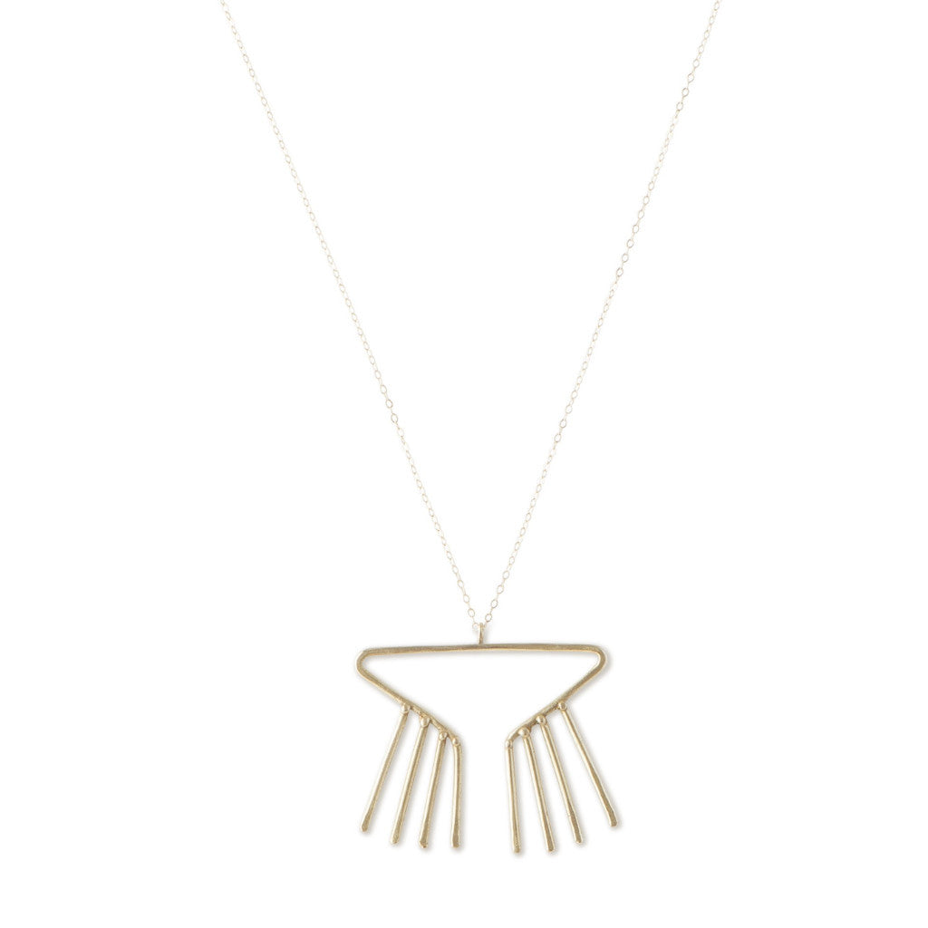 Close up of Sky Phaebl's Merak bronze necklace. Open triangular pendant with fixed fringe and slight hammer texture on fine gold-filled chain.