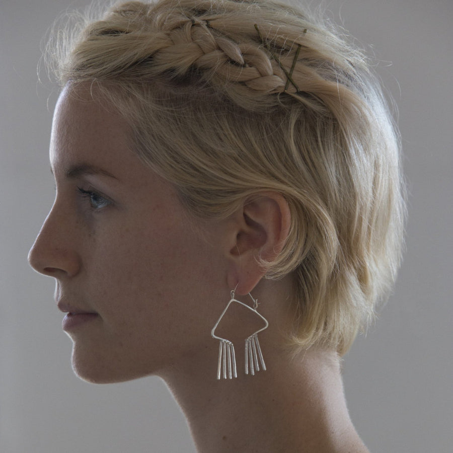 Model wears obtuse, open triangular earring with hammer textured fixed fringe.